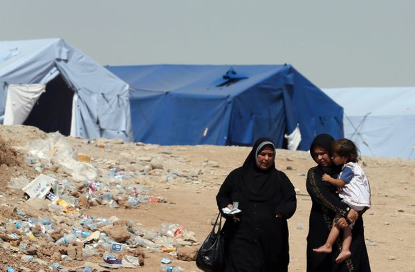 Iraqi women walk in the temporary camp set up to house civilians fleeing violence