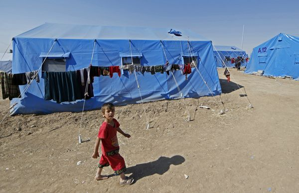 An Iraqi boy plays at a temporary camp set up to house civilians fleeing violence