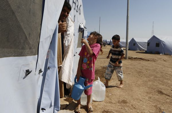 Iraqi families arrive at a temporary camp set up to house civilians fleeing violence