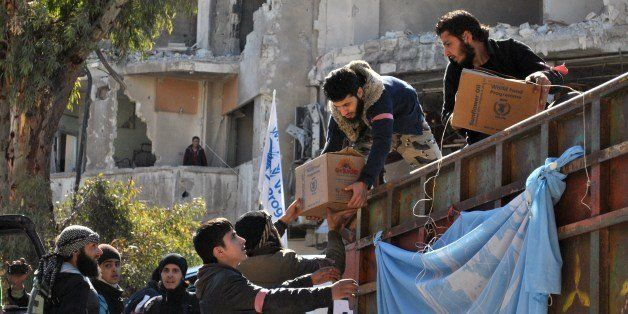 Rebel fighters help unload aid food during a UN-led humanitarian operation in the besieged Syrian city of Homs on February 12