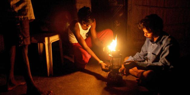 TO GO WITH Lifestyle-India-economy-energy by N. Suresh Indian men light up a kerosene petromax lamp in their home in the trib