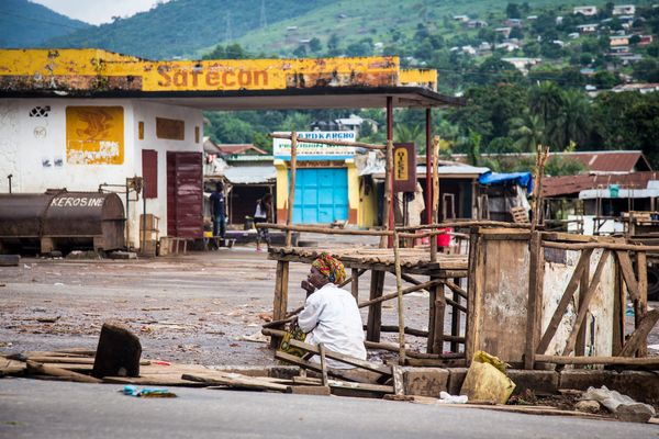 A trader sits at an empty local market area in Waterloo, as Sierra Leone government enforces a three day lock down on movemen