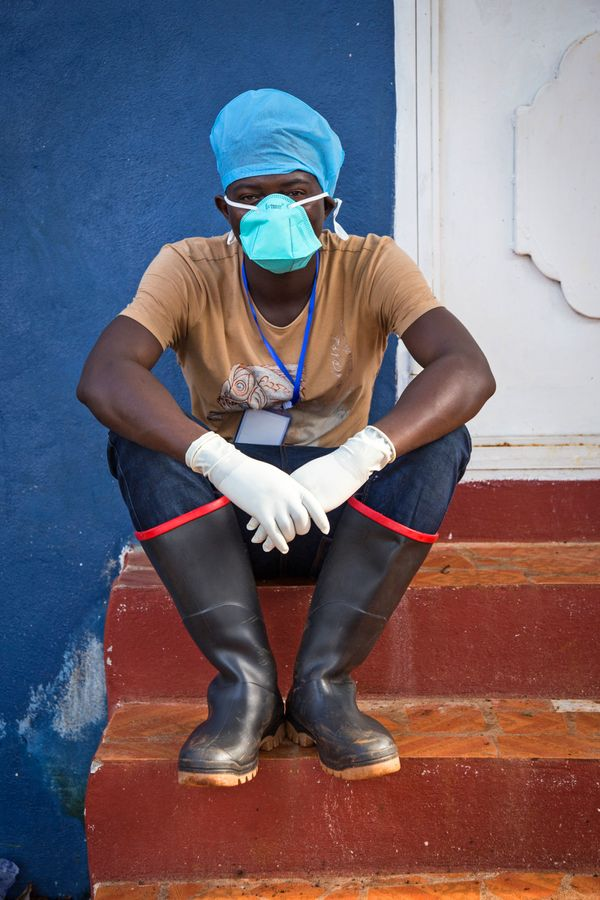 In this Sept. 19, 2014 photo, an Ebola virus health care worker takes a rest outside a Ebola isolation unit in Freetown, Sier