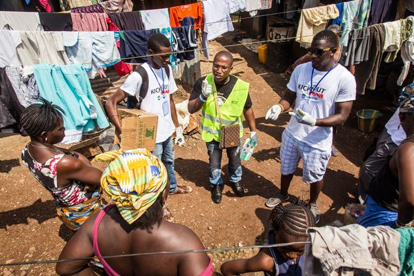 A health worker volunteer talks with residents on how to prevent and identify the Ebola virus in others, and distributes bars