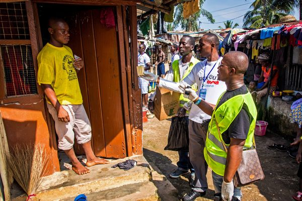 Health worker volunteers talk to a resident to distribute bars of soap and information about Ebola in Freetown, Sierra Leone,