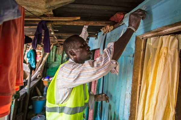 A health worker volunteer marks a home with chalk to identify that it has been visited, as they distribute bars of soap and i