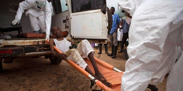 In this photo taken on Wednesday, Sept. 24, 2014, healthcare workers load a man suspected of suffering from the Ebola virus o