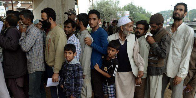 Flood-affected Kashmiris wait in line to meet Indian armed forces doctors at a temporary medical camp established underneath