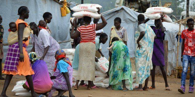 Women carry maize flour sacks during a food distribution by the Catholic Church to refugees and displaced people in Juba on A