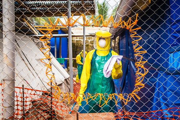 Healthcare workers in protective gear work at an Ebola treatment center in the west of Freetown, Sierra Leone