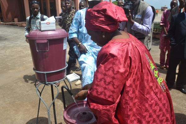 African Union Chairperson Nkosazana Dlamini-Zuma washes her hands as she arrives in Conakry