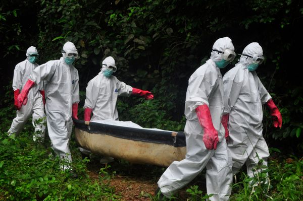 A burial team in protective gear carry the body of woman suspected to have died from the Ebola virus in Monrovia, Liberia