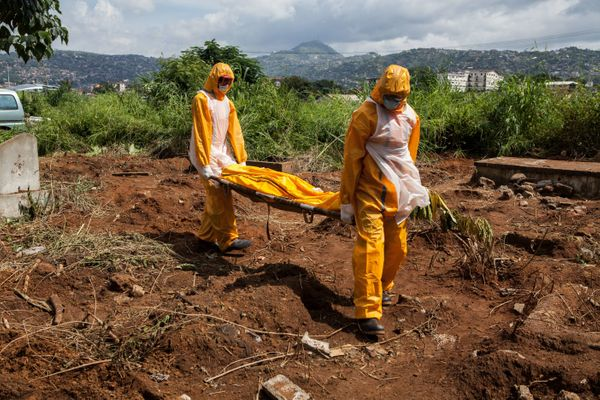 A team of funeral agents specialised in the burial of  victims of the Ebola virus carry a body prior to put it in a grave at