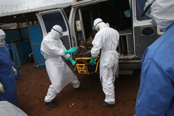 A burial team unloads an Ebola victim, who died in an ambulance, while collecting him for cremation