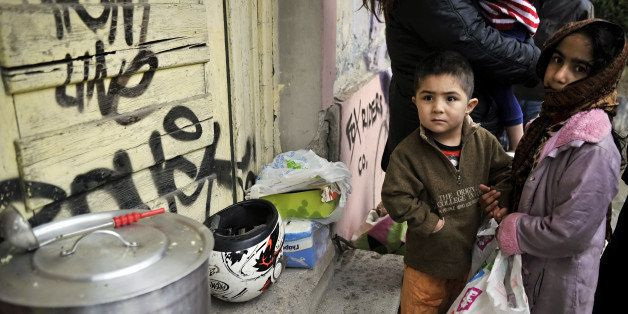 Immigrant children wait for food donated by activists from a soup kitchen, in a poor neighborhood in Athens, on February 6, 2
