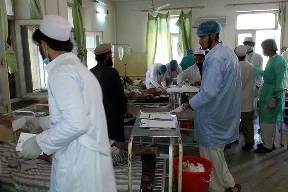 Afghan doctors assist civilians who were wounded when a suicide bomber detonated his explosives-packed vehicle near a crowded