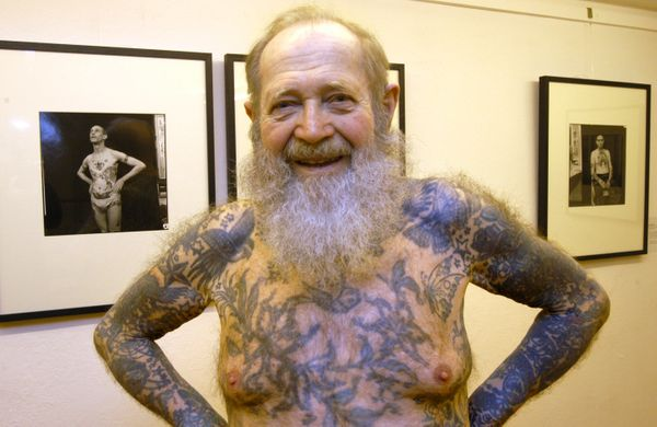 87-year-old photographer and tattoo artist Herbert Hoffmann poses in front of his photographs before a 2006 exhibition of his