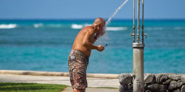 With the blue waters of Waikiki in the background, a man shaves at a public shower at Kapiolani Park, Wednesday, May 11, 2011