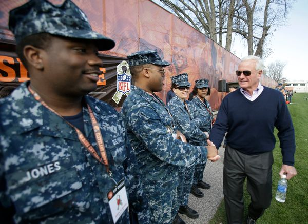 Cleveland Browns owner Jimmy Haslam shakes hands with military guests during practice at the NFL football team's training cam