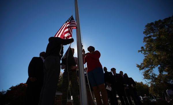 Iraq and Afghanistan war veterans raise the American flag during a Veterans Day ceremony at the Atlanta History Center, Tuesd