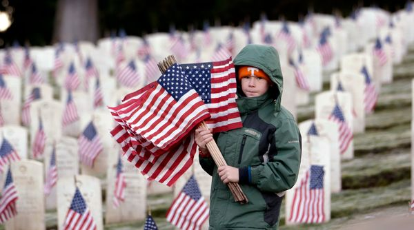 Cliff Knechtel, 12, a Boy Scout from Edmonds, Wash., Troop 300, carries a bundle of flags after helping to place others on gr