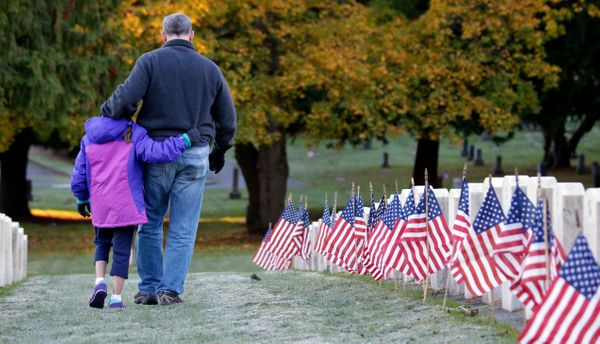 Maddie Nistl, 9, walks with her father, Dee Nistl, an Air Force veteran, past  flag-covered graves placed for Veterans Day in