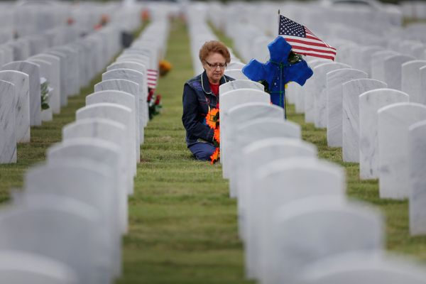 A woman knees at a headstone after placing a U.S. flag and cross at Fort San Houston National Cemetery, Tuesday, Nov. 11, 201