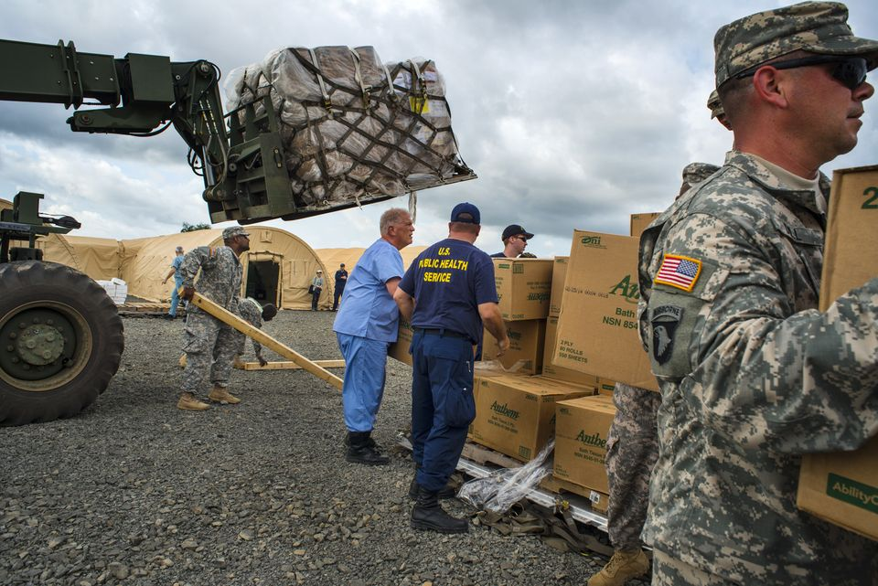 MONROVIA, LIBERIA-NOVEMBER 4:   U.S. military and the U.S. Public Health Service (USPHS) staff unload cargo at the Monrovia M