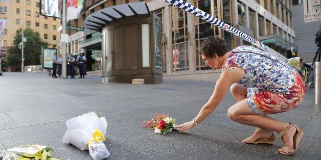 SYDNEY, AUSTRALIA - DECEMBER 16:  A woman cries as she leaves flowers to pay her respects at Martin Place on December 16, 201