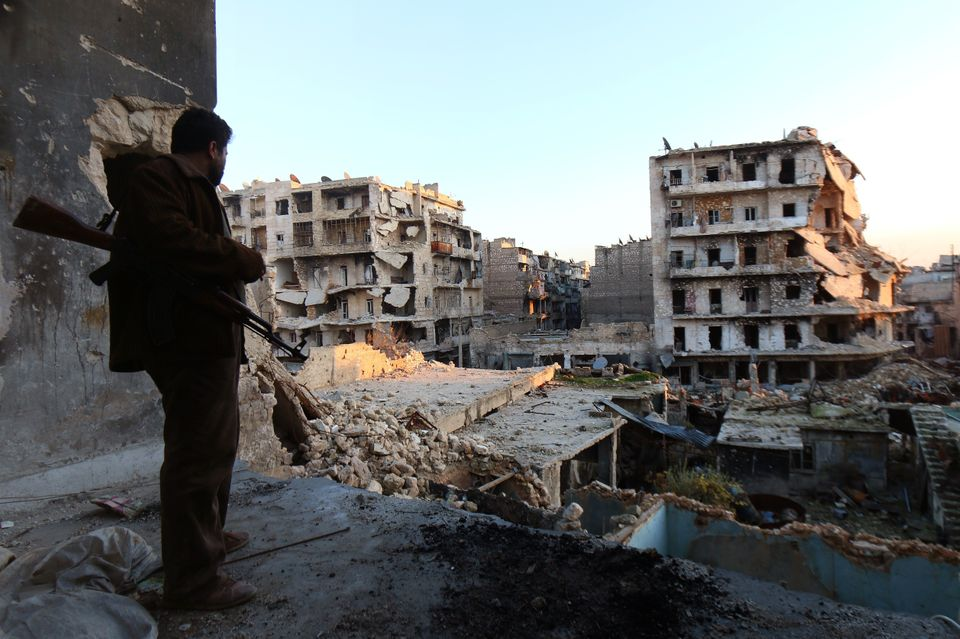 A rebel fighter stands in a building overlooking the damage from fighting in the city of Aleppo on December 16, 2013. (ZEIN A