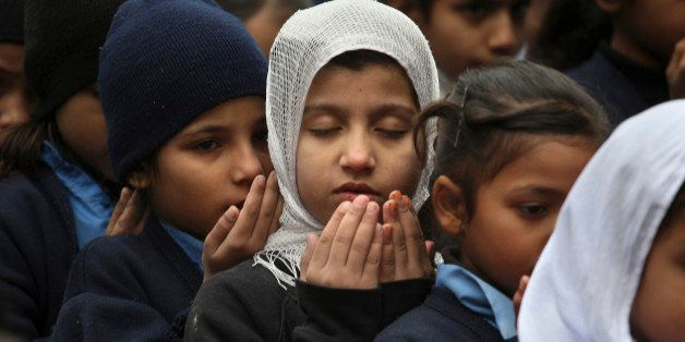 Pakistani students pray during a special ceremony for the victims of Tuesday's school attack in Peshawar, at a school in Laho