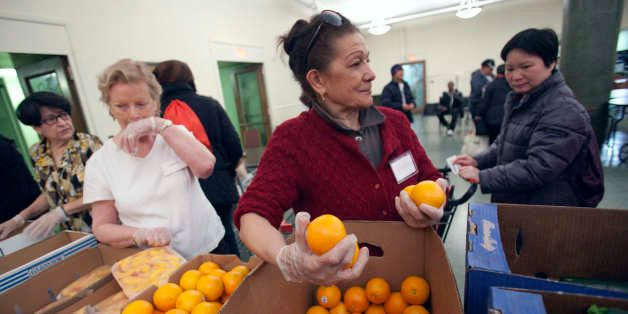 Volunteer Caroline Osterman, center, of Boston, distributes oranges in the Franciscan Food Center food pantry at St. Anthony