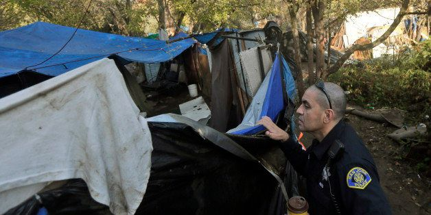 San Jose police officer Eduardo Sandoval looks inside a makeshift tent as notices to move are handed out at the Silicon Valle