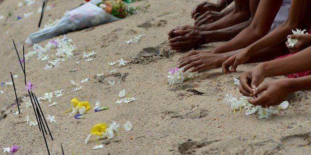 Sri Lankan women commemorate the victims of the December 2004 tsunami, offering flowers, prayers and alms during a special ce