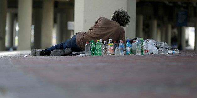 A homeless man lies under the Pontchartrain Expressway overpass, where up to 150 homeless live, in New Orleans on Wednesday,