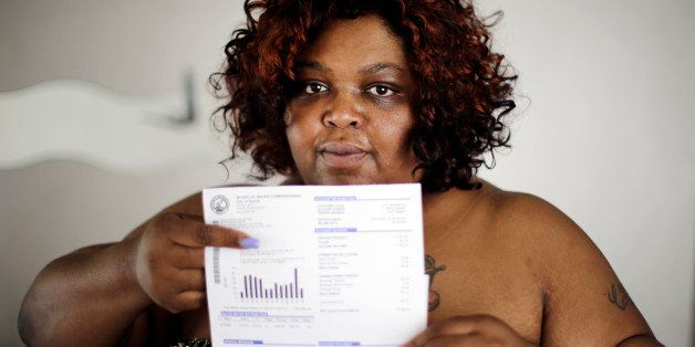 Nicole Hill holds up her past due water bill at her home in Detroit Wednesday, June 25, 2014. Detroit Water department spokes