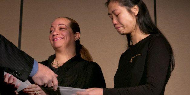 Maritza Ramos, left, and Pei Xia Chen, widows of slain New York City Police Officers Rafael Ramos and Wenjian Liu, receive ch