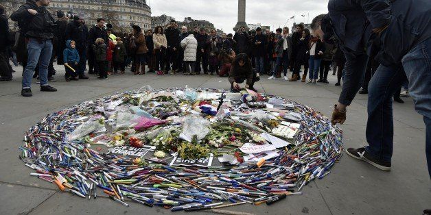 People arrange pens, pencils and flowers as a tribute during a gathering in Trafalgar Square in central London on January 11,