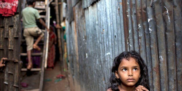 A Bangladeshi child stands in an alley as a boy climbs a ladder outside their home at a slum in Dhaka, Bangladesh, Friday, Oc
