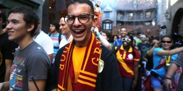 Cheering fans react to being welcomed into a confetti-filled Diagon Alley during the grand opening at the Wizarding World of