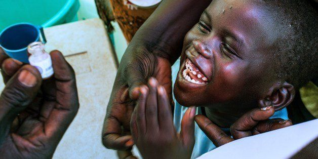 A child smiles as he prepares to receive a dose of oral cholera vaccine inside a tent of the United Nation Mission in South S