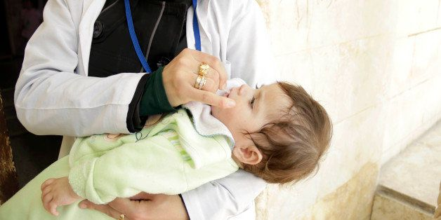 ALEPPO, SYRIA - MAY 5:  A health worker gives polio vaccine drops to a Syrian child during the polio vaccination campaign org