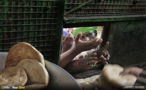 """인도의 식량 배급 풍경. """"나는 이 사진을 통해 아직 인도에 빈곤이 만면하다는 사실을 전하고 싶다. 손을 내민 사람의 날카로운 눈빛이 사태의 심각성을 전하고 있다. """""""