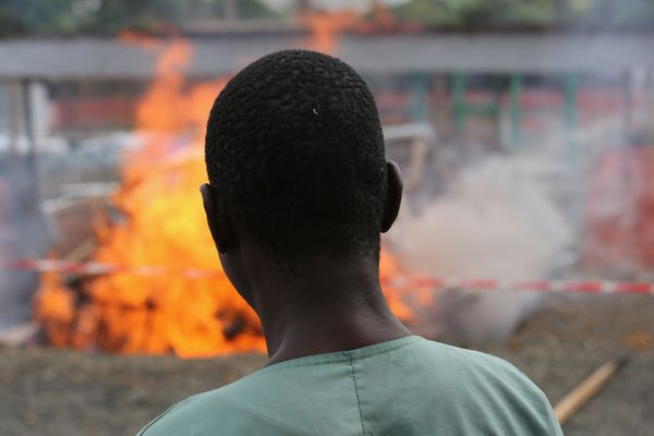 Ebola survivor Jessy Amos, 45, now an employee of Doctors Without Borders (MSF), watches after setting fire to part of the Eb