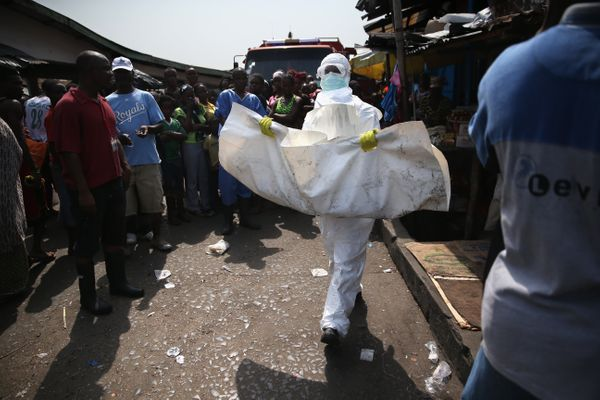 A Liberian Red Cross burial team in Ebola protectant clothing collects the body of a toddler from a home in the West Point to