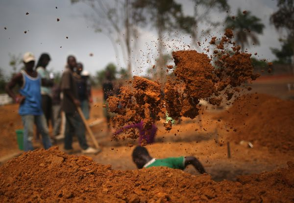 A grave digger works in a cemetery for 'safe burials' in Disco Hill, Liberia on Jan. 27, 2015. The cemetery, operated by <a h
