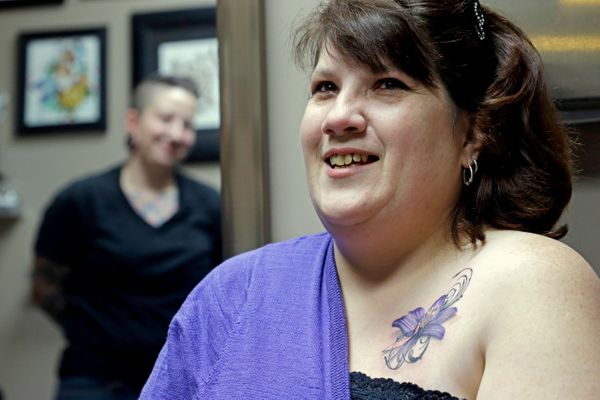 In this Wednesday, Dec. 17, 2014 photo, tattoo artist Ashley Neumann, left, watches as breast cancer survivor Mari Jankowski