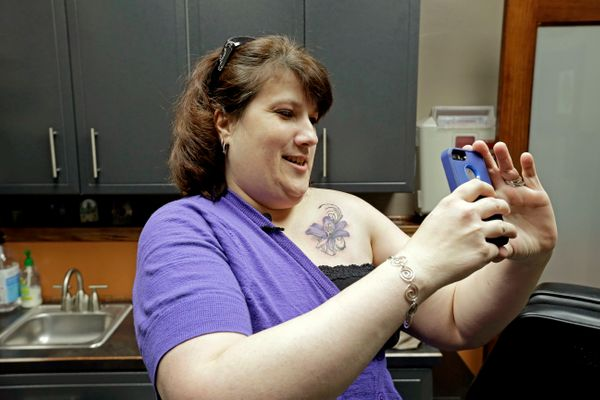 In this Wednesday, Dec. 17, 2014 photo, breast cancer survivor Mari Jankowski takes a photo of her new tattoo that covers a s