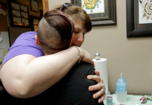 In this Wednesday, Dec. 17, 2014 photo, tattoo artist Ashley Neumann is hugged by breast cancer survivor Mari Jankowski after