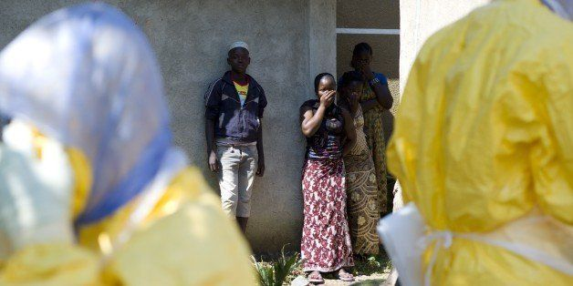 People react as Guinean Red Cross workers arrive to remove the corpse of a neighbour who died of Ebola in Macenta on November